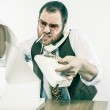 Irate chief at desk holding rotary phone in anger reading over fax — Stock Photo