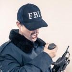Furious FBI man bearing teeth under cap, blue jacket on vintage radio — Stock Photo #10648505