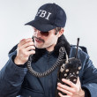 Head down FBI agent in blue jacket talking over vintage radio — Stok fotoğraf