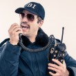 Stock Photo: FBI agent in blue riot jacket talking loudly on vintage radio
