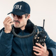 Young white FBI officer in blue jacket talking on vintage radio — Stock Photo #10648678