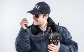 Angry FBI agent in situaiton with blue jacket, retro radio, and cap — Stock Photo