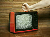 Fist smashing a TV — Stock Photo