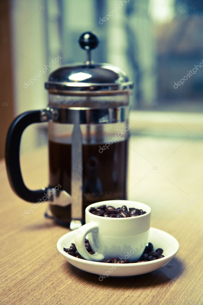 A blue hued french press and white coffee mug on a small white plate filled with dark roasted coffee beans.  The mug is on a cherry wood table. — Stock Photo #8675937