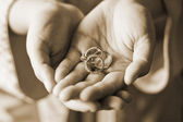 Sephia Styled Closeup View Two Hands Holding Three Wedding Rings — Stok fotoğraf