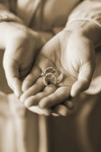 Sephia Hued Brides Mother holding the engaged couples wedding rings — Stock Photo
