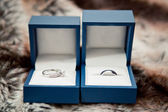 Two Blue Boxes Containing wedding rings on textured table — Stock Photo