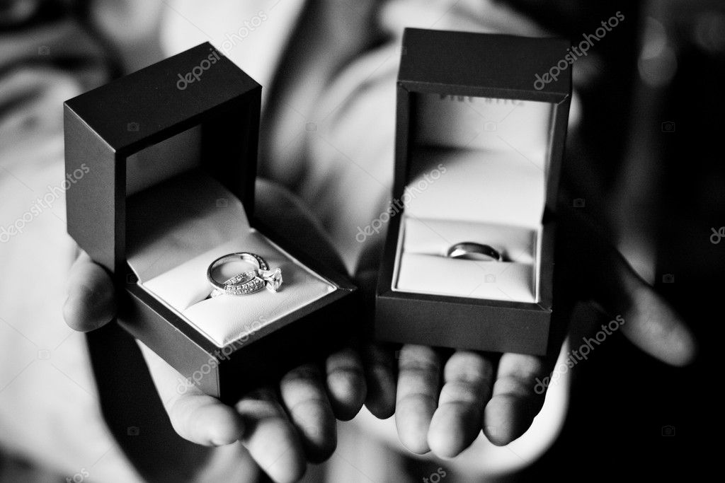 Black White ring bearer holding married couples wedding bands two elegant boxes.  grooms band in bearers left hand brides diamond ring in bearers right hand.  Stock Photo #9196258