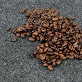 Granos de café sobre un fondo gris — Foto de Stock
