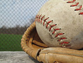 Beautiful old softball with shallow depth of field in a vintage mitt on the sidelines — Stock Photo