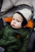 Lindo niño sentado en una silla de ruedas y mirando reflexivamente — Foto de Stock