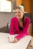 Aantrekkelijke vrouw in de keuken met een koffiekopje — Stockfoto