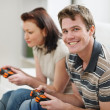 Young man playing on console with girlfriend — Stock Photo