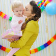 Mother kissing baby on birthday celebration party — Stock Photo