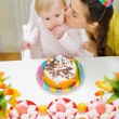 Mother kissing baby eating birthday cake — Stock Photo