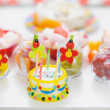 Closeup on table with sweets and birthday candle cake — Stock Photo #10552822