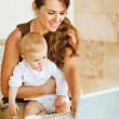 Young mother working with baby on laptop — Stock Photo #10552901