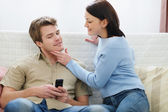 Young woman trying to distract boyfriend from mobile phone — Stock Photo