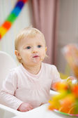 Portrait of thoughtful baby sitting at table — Stock Photo