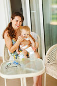 Young mama feeding baby on terrace — Stock Photo