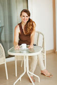 Smiling young woman sitting on terrace and having coffee — Stock Photo