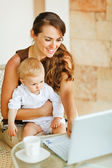 Young mother working with baby on laptop — Stock Photo