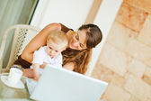 Baby sitting on mothers laps and working on laptop — Stock Photo