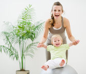 Mother and baby playing with fitness ball — Stock Photo