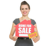 Happy realtor showing home for sale sold sign — Stock Photo