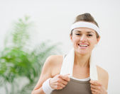 Portrait of happy fitness woman with towel on shoulders — Stock Photo