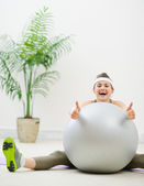 Smiling woman sitting behind fitness ball and showing thumbs up — Stock Photo