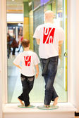Two dummies in symbolizing discount shirts shot from behind — Stock Photo