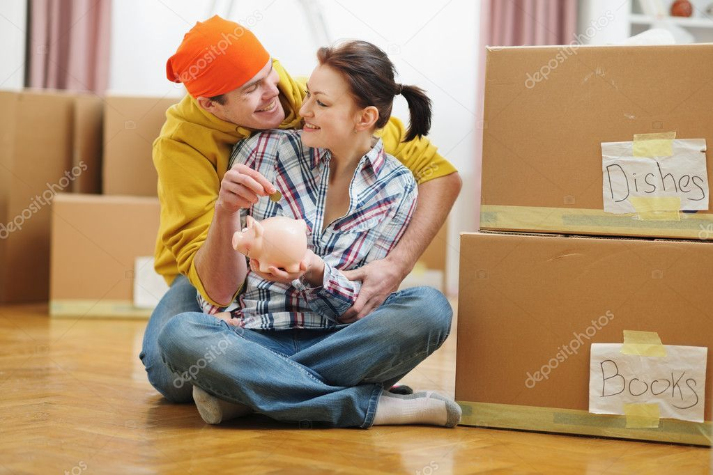Young couple among boxes putting coin in piggy bank — Stock Photo #10552631