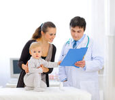 Interested baby touching patients card while pediatrician talkin — Stock Photo