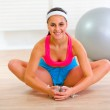 Smiling girl doing stretching exercises at home — Stock Photo
