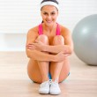 Smiling fit girl in sportswear sitting on floor at home — Stock Photo