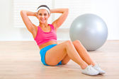 Happy fitness girl doing abdominal crunch on floor — Stock Photo