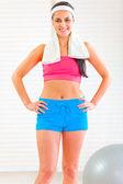 Happy fitness girl with towel around neck — Stock Photo