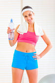 Smiling girl with towel around neck holding bottle of water — Stock Photo