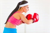 Concentrated fitness woman in boxing gloves working out — Stock Photo