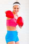 Smiling fitness girl in boxing gloves punching — Stock Photo