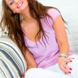 Stock Photo: Happy pretty young womsitting on white couch