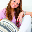 Smiling beautiful young woman relaxing on white divan — Stock Photo