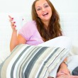 Laughing pretty woman relaxing on sofa with cup of coffee - Stock fotografie