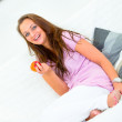 Pleased pretty woman sitting on couch and holding apple in hand — Stock Photo