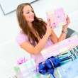 Pleased pretty woman sitting on sofa and holding present in hands - ストック写真