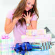 Surprised pretty woman sitting on sofa and looking at presents - 图库照片