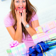 Surprised woman sitting among gifts and holding hands near head - ストック写真