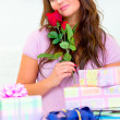 Dreamy pretty woman sitting among gifts and holding rose - 图库照片