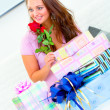 Smiling pretty woman sitting among gifts and holding rose - 图库照片